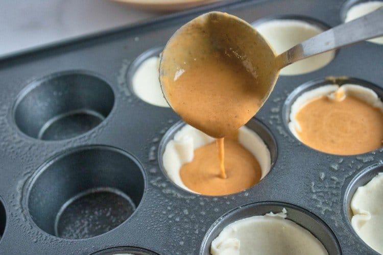 Spoon pumpkin pie filling into mini pie crusts