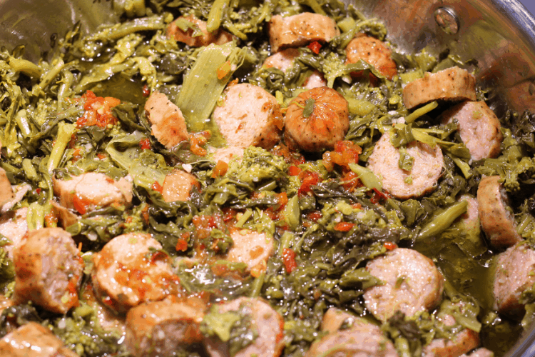 large skillet with rapini, sausage, hot peppers