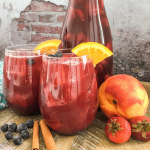 sangria in wine glasses with peaches and berries